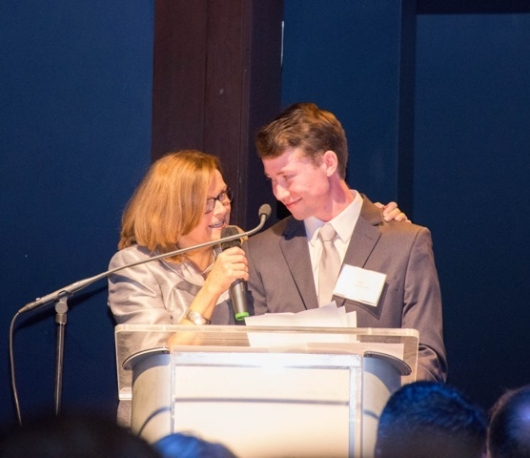SOWMA Executive Director Cheryl Opper with Zachary as he responds to a standing ovation after speaking at the Open the Door Gala